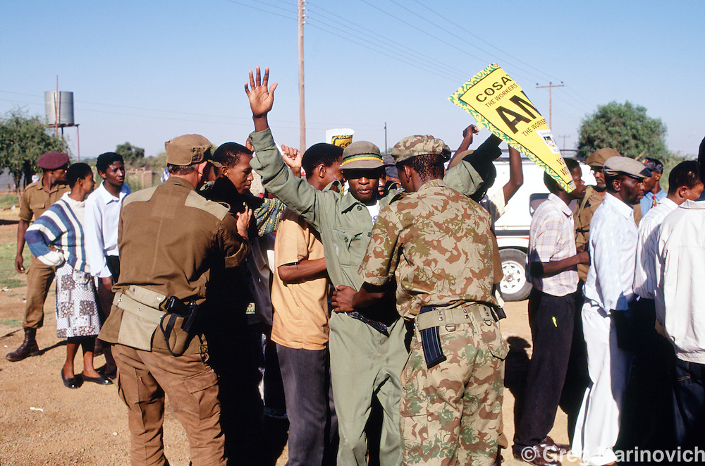 Police search an ANC supporter at a rally ahead of the 1994 elections in South Africa.