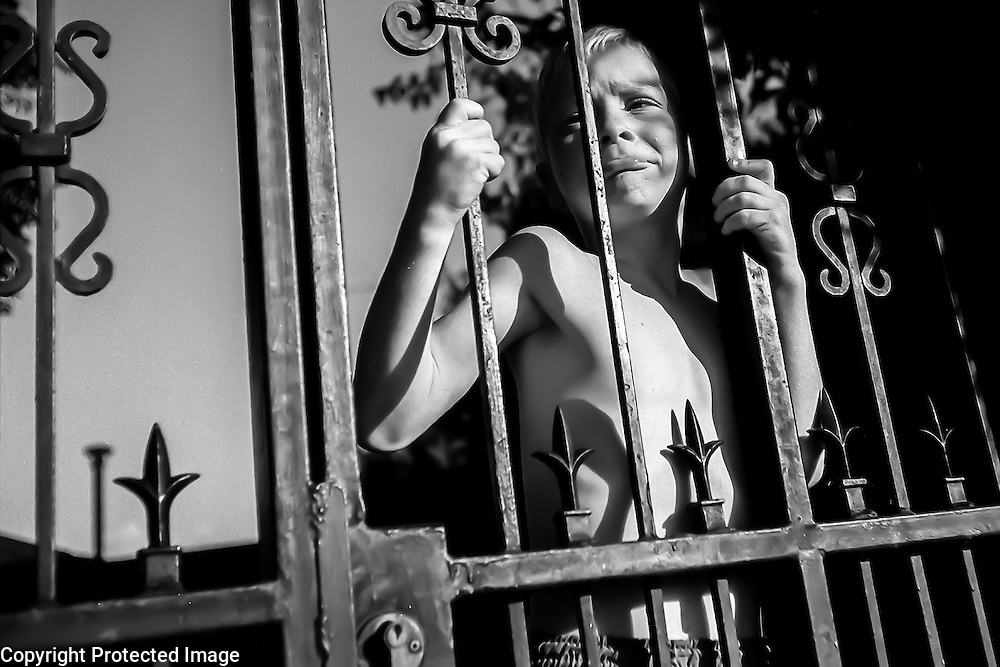 Matthew Blackburn makes a sad face through the Blackburns' security gate. Matthew lives with his parents and two brothers in a predominantly white suburb of Johannesburg.  Because of South Africa's high crime and murder rate, most whites live behind locked gates and have sophisticated security systems as well as dogs.
