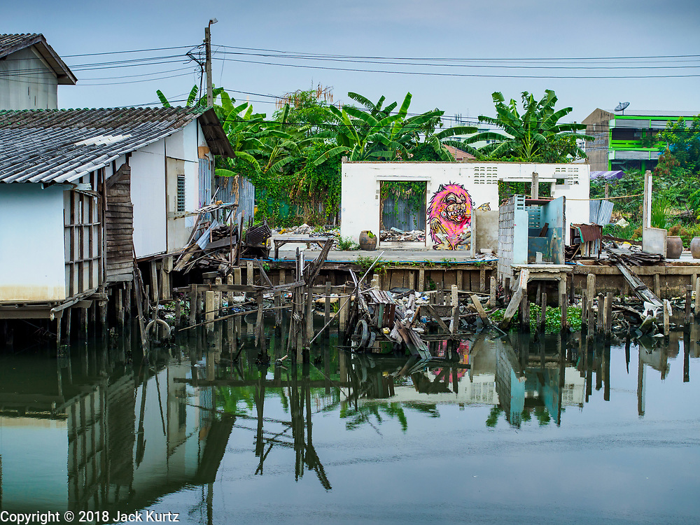 """22 MARCH 2018 - BANGKOK, THAILAND: Khlong Lat Phrao. Bangkok officials are evicting about 1,000 families who have set up homes along Khlong  Lat Phrao in Bangkok, the city says they are """"encroaching"""" on the khlong. Although some of the families have been living along the khlong (Thai for """"canal"""") for generations, they don't have title to the property, and the city considers them squatters. The city says the residents are being evicted so the city can build new embankments to control flooding. Most of the residents have agreed to leave, but negotiations over compensation are continuing for residents who can't afford to move.      PHOTO BY JACK KURTZ"""