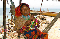 Kuna Indian woman wearing native costume (with Mola embroderies) sits in a hammock on Corbisky Island, San Blas Islands (Kuna Yala), Caribbean Sea, Panama
