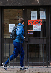 © Licensed to London News Pictures. 15/03/2020. London, UK. A man looks at a 'STOP' sign on the door of Wapping Health Centre in east London. Wapping Health Centre has announced that from Monday 16th March, all new appointments at the GP surgery will be made by telephone triage only, to minimise cross infection and protect their medical workforce from coronavirus and has stated that any patients with pre-booked appointments next week should not come into the surgery but instead wait for a telephone call from their doctor. Photo credit: Vickie Flores/LNP