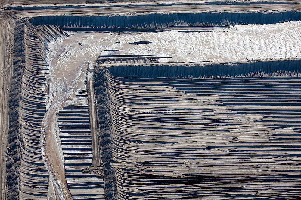 A stream of wastewater passes through an earthen channel at a Suncor mine