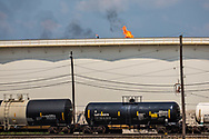 Flare  behind oil tank and train carrying toxic cargo at Exxon's Refinery in Beaumont, Texas  after Hurricane Harvey.