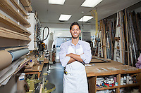 Portrait of a happy young craftsman standing with arms crossed in workshop
