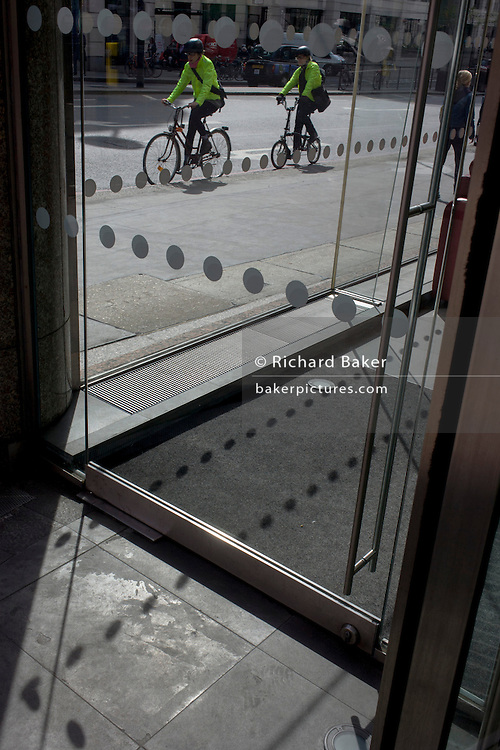 Cyclists pedal past an office foyer entrance featuring dots and circles (and shadows) on exterior windows in the City of London.