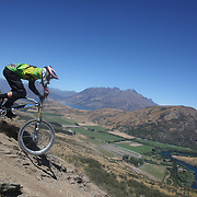 Thomas Jeandin from Switzerland in action during the New Zealand South Island Downhill Cup Mountain Bike series held on The Remarkables face with a stunning backdrop of the Wakatipu Basin. 150 riders took part in the two day event. Queenstown, Otago, New Zealand. 9th January 2012. Photo Tim Clayton
