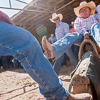 070313       Cable Hoover<br /> <br /> Demetrius Begay practices his bronco riding technique under the guidance of pro rider Forest Bramwell, center, during a PRCA camp at the Navajo Nation Fairground in Window Rock Wednesday.
