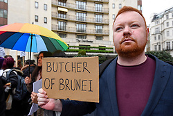 © Licensed to London News Pictures. 06/04/2019. LONDON, UK.  A member of the LGBT community with a sign during a protest outside the Brunei-owned Dorchester Hotel in reaction to reports that the Sultan of Brunei decreed that adultery and gay sex is punishable by death by stoning in the Islamic sultanate.  Several large clients of the Dorchester Hotel have already ceased bookings in response to the decree.  Photo credit: Stephen Chung/LNP