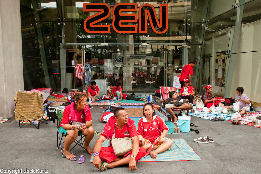 18 APRIL 2010 -- BANGKOK, THAILAND: Red Shirts sit in the shade in front of the entrance to ZEN, one of the department stores closed by the Red Shirts rally. The Red Shirts protest in the Ratchaprasong Shopping district, home to Bangkok's most upscale malls, is costing the Thai economy millions of Baht per day because the malls and most of the restaurants are closed and tourists are staying away from the area. But that hasn't stopped the Red Shirts who have brought their own economy with them. There are Red Shirt restaurants, food stands, souvenir vendors and more, creating a micro economy for Red Shirts in the area.  The Red Shirts continue to occupy Ratchaprasong Intersection an the high end shopping district of Bangkok. They are calling for Thai Prime Minister Abhisit Vejjajiva to step down and dissolve the parliament. Most of the Red Shirts support ousted former Prime Minister Thaksin Shinawatra.   PHOTO BY JACK KURTZ