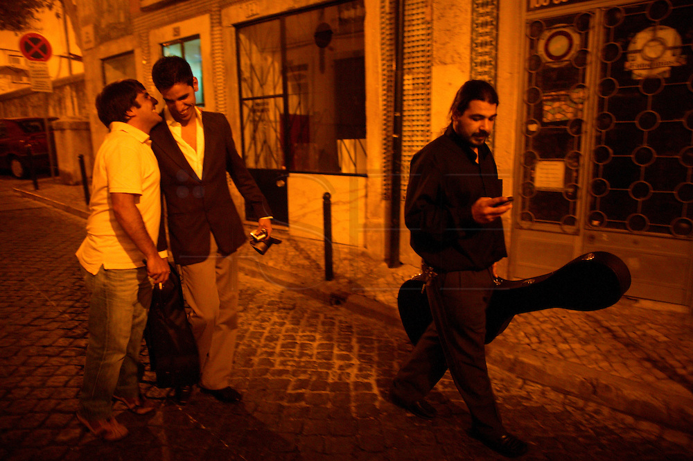 "Singer Pedro Moutinho along with Portuguese Guitar player Diogo Valente and bass player Joao Penedo walking at night after a performance at restaurant ""Mesa de Frades"", an old chapel in Alfama typical neighborhood"