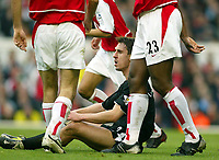Photo: Scott Heavey.Digitalsport<br /> Arseanl v Manchester United. FA Barclaycard Premiership. 28/03/2004.<br /> Gary Neville sits among the Arsenal defenders and believes he should have had a penalty