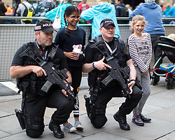© Licensed to London News Pictures . 28/05/2017 . Manchester , UK . Two children pose for a photo with armed police , who are watching over the run . The Great Manchester Run 2017 . Security is still heightened in Manchester following a murderous bomb attack at an Ariana Grande gig at Manchester Arena on Monday 22nd May . Photo credit : Joel Goodman/LNP