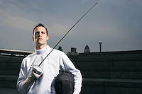 Fencer holding sword outdoors portrait