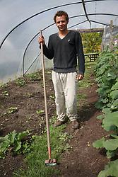 Trinity Organic Farm, Nottinghamshire - volunteer hoeing weeds in polytunnel