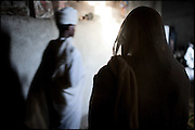 """A woman prays in a Orthodox Church, during the Sunday function. North West of Ethiopia, on sunday, Febrary 15 2009.....In a tangled mingling of tradition and culture, in the normal place of living, in a laid-back attitude. The background of Ethiopia's """"child brides"""", a country which has the distinction of having highest percentage in the practice of early marriages despite having a law that establishes 18 years as minimum age to get married. Celebrations that last days, their minds clouded by girls cups of tella and the unknown for the future. White bridal veil frame their faces expressive of small defenseless creatures, who at the age ranging from three to twelve years shall be given to young brides men adults already...To protect the identities of the recorded subjects names and specific places are fictional."""