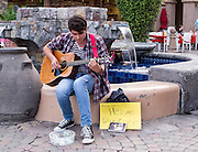 """""""Please help me get to college"""" this guitar player's sign reads.  It says it all. Palm Springs, California"""