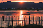 The sun sets over Inlé Lake, Burma (Myanmar) as fisherman finish up a day's work