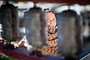 Old woman face between prayer wheels (Nepal).