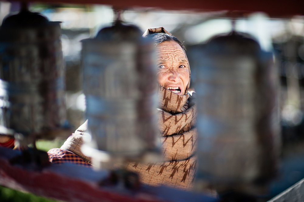 Old woman face between prayer wheels (Nepal).