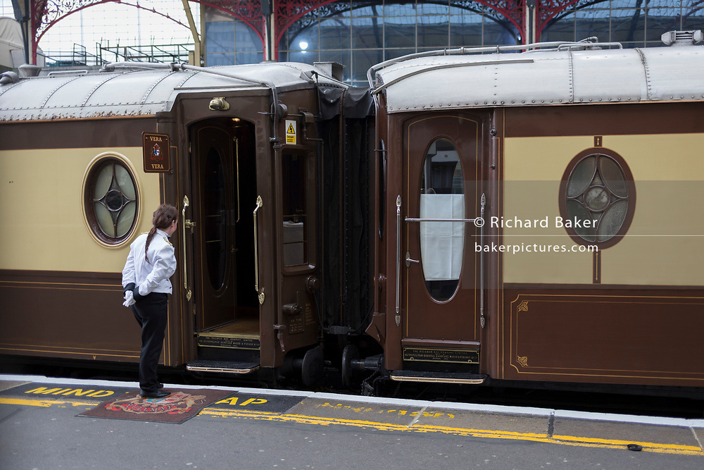 A steward waits to greet passengers for an Orient Express service from platform 2 at Victoria station, on 8th November 2019, in London, England.