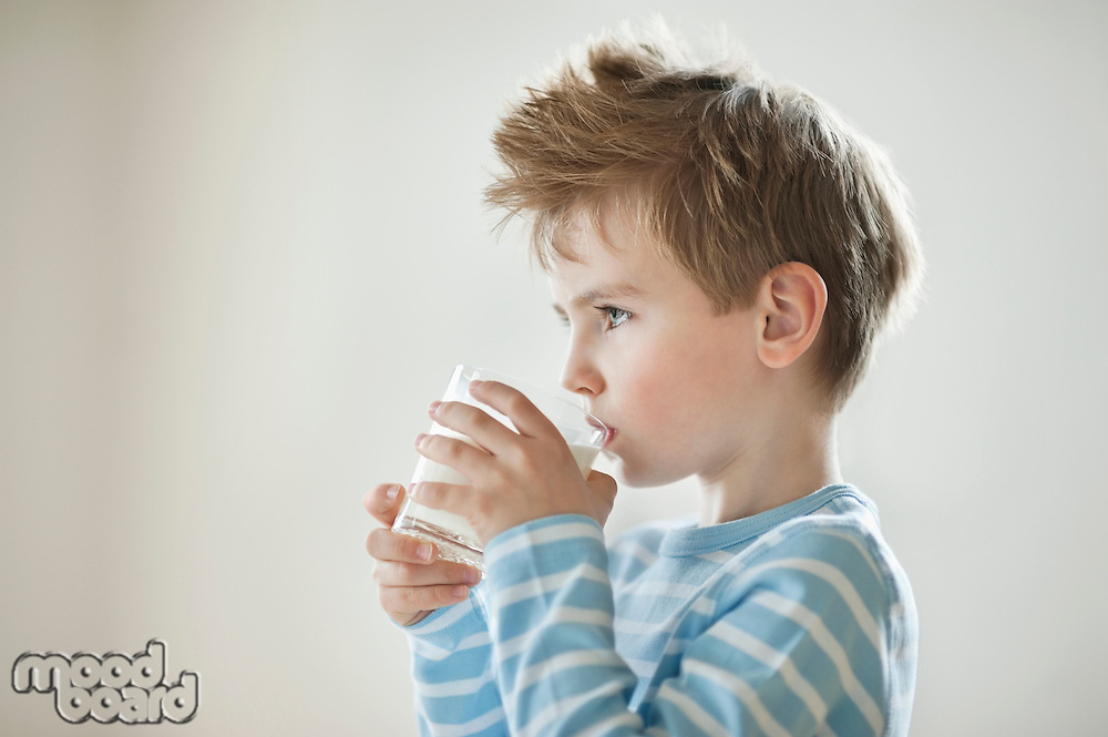 Side view of a young boy drinking milk
