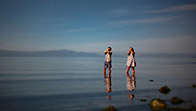 People stand in shallow water of low tide while watching a solar eclipse in Sechelt, BC.    (2017)