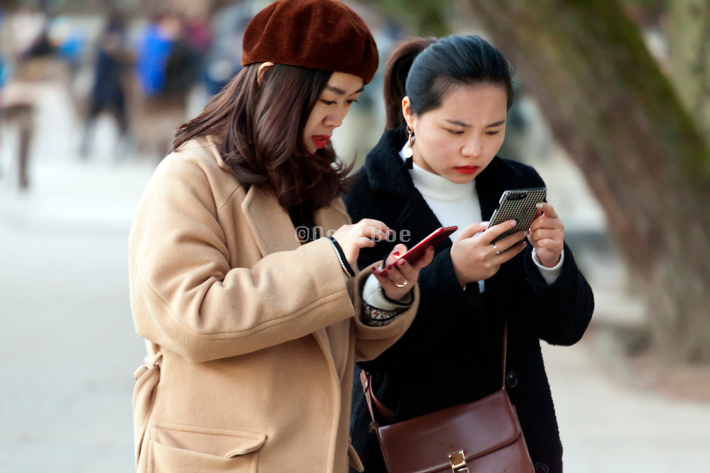 two Asian tourists intense busy with their smart phone