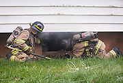 Two firefighters peer through a broken window of a basement in a residential house that is on fire.