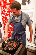 Flushng, NY - February 25, 2017. Huge Dufour from M Wells Steakhouse in Long Island City, Queens, cooking blood sausage at the 2017 Charcuterie Masters at Flushing Town Hall.
