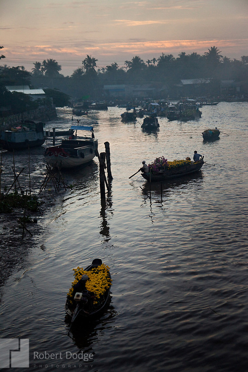 Two boats laden with yellow flowers make their way to the floating market in Soc Trang Province at the first sign of morning light. The flowers are purchased and kept at home for good luck during the Tet, the Lunar New Year. Robert Dodge, a Washington DC photographer and writer, has been working on his Vietnam 40 Years Later project since 2005. The project has taken him throughout Vietnam, including Hanoi, Ho Chi Minh City (Saigon), Nha Trang, Mue Nie, Phan Thiet, the Mekong, Sapa, Ninh Binh and the Perfume Pagoda. His images capture scenes and people from women in conical hats planting rice along the Red River in the north to men and women working in the floating markets on the Mekong River and its tributaries. Robert's project also captures the traditions of ancient Asia in the rural markets, Buddhist Monasteries and the celebrations around Tet, the Lunar New Year. Also to be found are images of the emerging modern Vietnam, such as young people eating and drinking and embracing the fashions and music of the West. His book. Vietnam 40 Years Later, was published March 2014 by Damiani Editore of Italy.