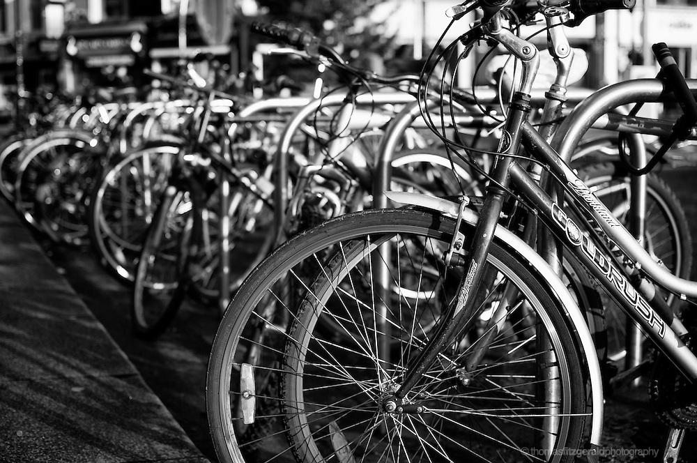 Dublin City, Ireland: A large number of bikes are parked at bike racks in Dublin City with one bike in focus and the rest out of focus