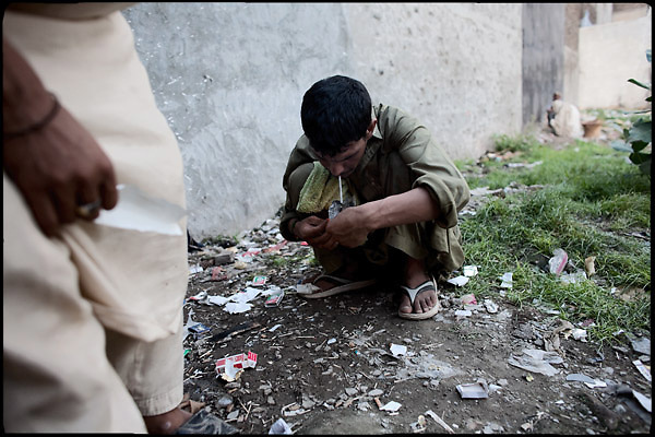 """A young drug addict smokes his heroin's dose. People, who abuse those substances, consume dope three times per day. Morgh Mandi, Rawalpindi, Pakistan, on thursday, August 14 2008.....""""Pakistan is one of the countries hardest hits by the narcotics abuse into the world, during the last years it is facing a dramatic crisis as it regards the heroin consumption. The Unodc (United Nations Office on Drugs and Crime) has reported a conspicuous decline in heroin production in Southeast Asia, while damage to a big expansion in Southwest Asia. Pakistan falls under the Golden Crescent, which is one of the two major illicit opium producing centres in Asia, situated in the mountain area at the borderline between Iran, Afghanistan and Pakistan itself. .During the last 20 years drug trafficking is flourishing in the Country. It is the key transit point for Afghan drugs, including heroin, opium, morphine, and hashish, bound for Western countries, the Arab states of the Persian Gulf and Africa..Hashish and heroin seem to be the preferred drugs prevalence among males in the age bracket of 15-45 years, women comprise only 3%. More then 5% of whole country's population (constituted by around 170 milion individuals),  are regular heroin users, this abuse is conspicuous as more of an urban phenomenon. The substance is usually smoked or the smoke is inhaled, while small number of injection cases have begun to emerge in some few areas..Statistics say, drug addicts have six years of education. Heroin has been identified as the drug predominantly responsible for creating unrest in the society."""""""