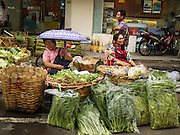 24 FEBRUARY 2016 - BANGKOK, THAILAND:  Women sell produce from a street stall in Pak Khlong Talat in Bangkok. Bangkok government officials announced this week that vendors in Pak Khlong Talat, Bangkok's well known flower market, don't have to move out on February 28. City officials are trying to clear Bangkok's congested sidewalks and they've cracked down on sidewalk vendors. Several popular sidewalk markets have been closed in recent months and the sidewalk vendors at the flower market had been told they would be evicted at the end of the month but after meeting with vendors and other stake holders city officials relented and said vendors could remain but under stricter guidelines regarding sales hours. The flower market is one of the best known markets in Bangkok and has become a popular tourist destination.       PHOTO BY JACK KURTZ