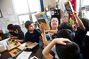Mrs. Jensen juggles reading and responding to the excitement of her kindergarten class as they explore educational magazines Feb. 28, 2014. Photo by Lauren Justice