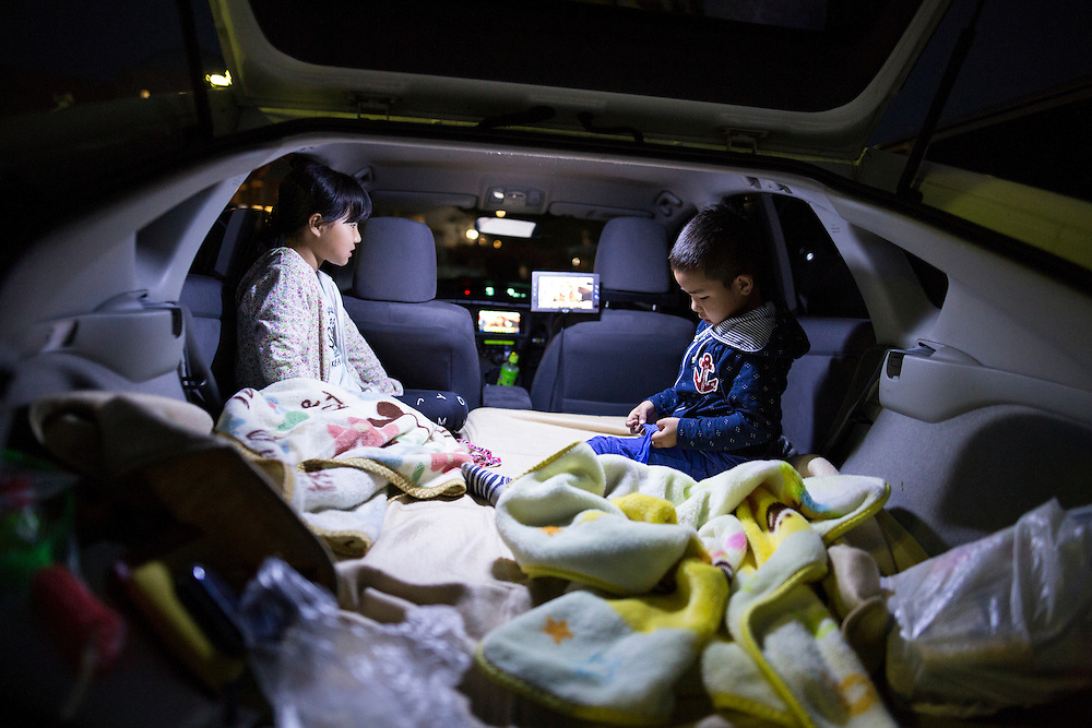 KUMAMOTO, JAPAN - APRIL 19: Kose (6year old) with his sister Misaki (9year old) watch animation inside their car before going to bed in the carpark of Mashiki Gymnasium evacuation center on April 19, 2016 in Mashiki, Kumamoto, Japan. This is the fourth day in the evacuation center since magnitude-6.3 quake hit Kumamoto city.<br /> <br /> Photo: Richard Atrero de Guzman