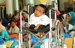 October 9, 2018 - Madiun, East Java, Indonesia - Sandi Sutriyono is 11 years old, the first child of two brothers married to the late Sutrisno-Sukiyatun, a resident of Rejosari Village, Sawahan Subdistrict, Madiun District, has been sitting for three years and is lying in a wheelchair. Because Sandi was still sitting in the third grade elementary school since she was sick. Even so that his physical condition is normal, the family carries a treatment password at a hospital in the Solo-Central Java area. But as long as Sandi underwent treatment, he did not get any results. Sandi continues to hope to recover from his illness, until he is physically normal and can go to school again like his age. To meet the economic needs of his family, the mother, Sukiyatun, had to work as a farm laborer in the fields and gardens of others. Sandi said he was happy, because it was invited by Madiun Regent Ahmad Dawami Ragil Saputro to receive compensation along with hundreds of orphans and other orphans in the Graha Pendopo Muda Madiun Regency (Credit Image: © Ajun Ally/Pacific Press via ZUMA Wire)