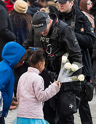 © Licensed to London News Pictures. 14/12/2017. London, UK. An armed police officer totals to a group of children who attended the service, outside St Paul's Cathedral in London following the Grenfell Tower National Memorial Service mark the six month anniversary of the Grenfell Tower fire. The service is attended by survivors of the fire and relatives of those who lost their lives in the fire, as well as members of the emergency services and members of the Royal family.  Over 70 people were killed when a huge fire ripped though 24-storey Grenfell Tower block in west London in June 2017.   Photo credit: Ben Cawthra/LNP