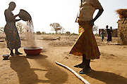 Mamata Kabore, pours sorghum from a height to separate grains from straw outside her home the village of Zarcin, Plateau-Centre region, Burkina Faso on Tuesday March 27, 2012.