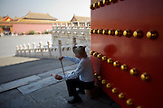 Gugong (Forbidden City, Imperial Palace). Elderly toursist having a rest at the gate next to Baohe Dian (Hall of Preserving Harmony).