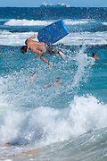 A boogie board and surfer go airborne at Sandy Beach on Oahu.