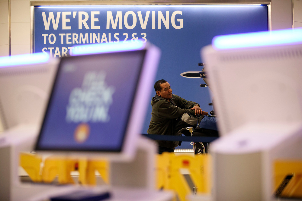 Francisco Gomez waits for a flight to El Salvador as he stands in front of Delta Airlines signage advising of the move while new kiosks for JetBlue check-in are barricaded  in Terminal 5 as the airline relocation begins at Los Angles International Airport (LAX) on Friday, May 12, 2017 in Los Angeles, Calif. Delta Airlines will move from Terminals 5 and 6 to Terminals 2 and 3, forcing 19 other carriers to shift their operations into the facilities vacated by Delta.  © 2017 Patrick T. Fallon