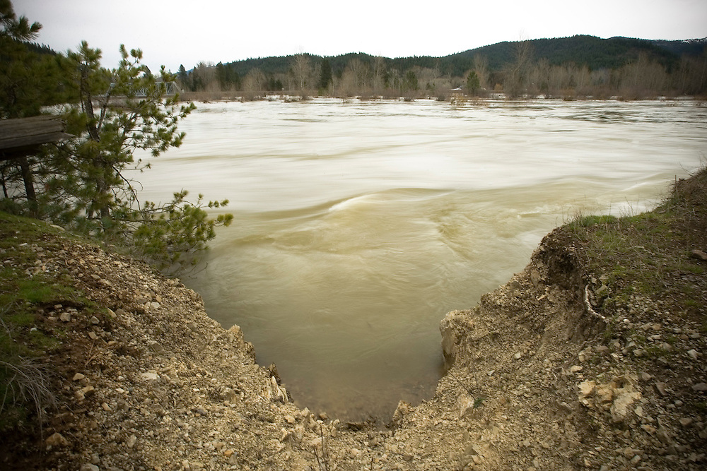 JEROME A. POLLOS/Press..Water rushes past a washed out section alongside CCC Road on the Coeur d'Alene River in Cataldo Monday afternoon following a flood warning issued by National Weather Service.