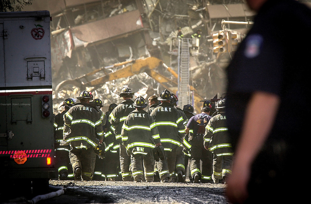 Firemen walk towards the remains of the North WTC Tower. Firemen, Medical personell and other rescue workers frantically search for possible survivors at the Ground Zero, World Trade Center site, the day after the terrorist attacks.