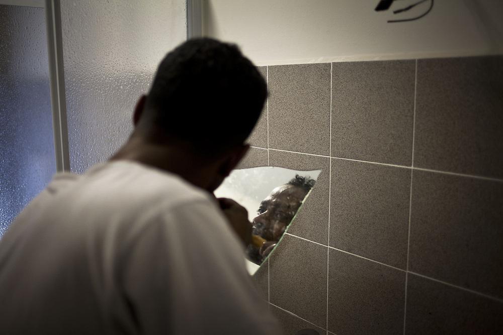 Un ragazzo si lava i denti. Interno ex palazzine olimpiche.