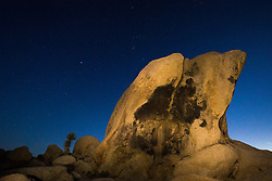 Nightt sky and stars on rock formations at White Tank, Joshua Tree National Park, California, USA.