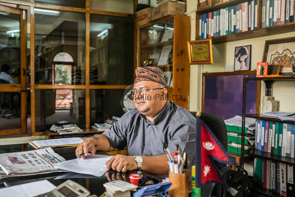 Father Silas Bogati, Director of Caritas Nepal since March 2016. He was celebrating the Holy Mass from the altar when a bomb exploded inside the Ascension church on the 23rd of May 2009. Here in his office at the Caritas headquarters next to the Church of the Ascension in Patan, Kathmandu, Nepal
