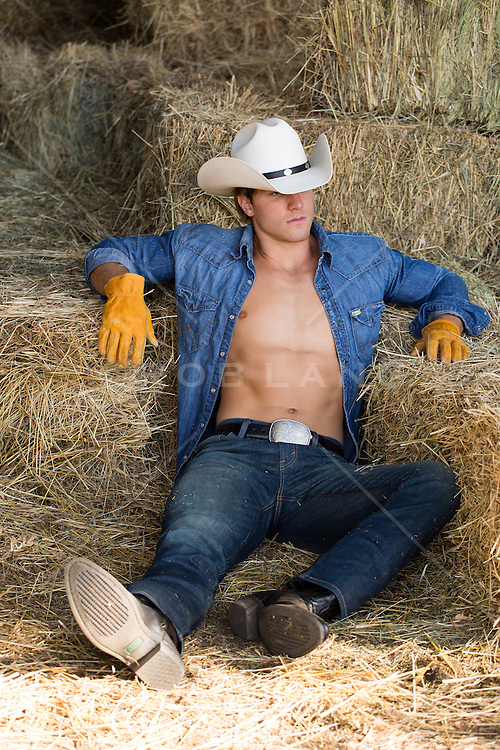 cowboy with an open shirt leaning against hay bales in a barn
