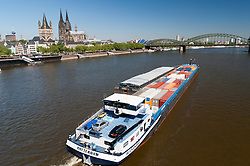 A Barge carrying shipping containers travels along the River Rhine in Cologne Germany