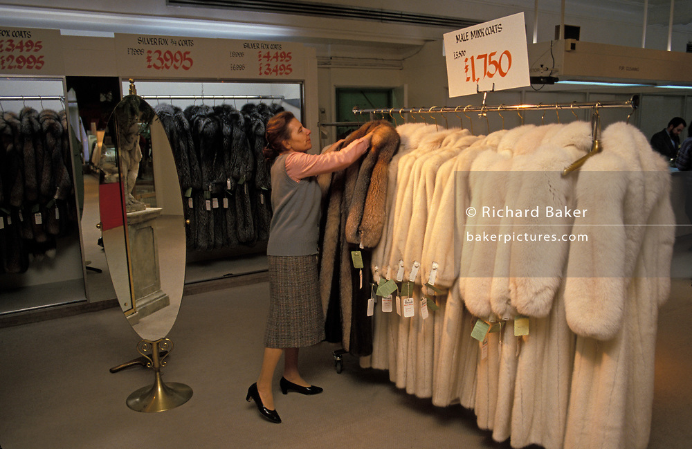 A shop assistant arranges male mink coats on sale from a rack on the shop floor of the Knightsbridge Harrods department store, on 17th March 1991, in London, England.