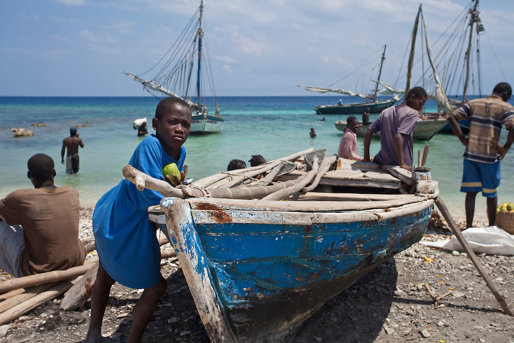 A child rests on a boat on the beach at Anse a Galet, Ile de la Gonave, Haiti
